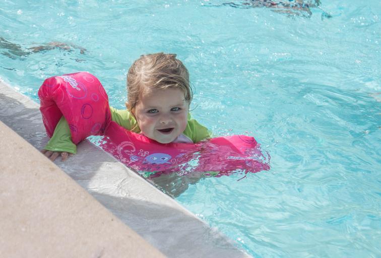 malé dítě plave v čisté vodě v bazénu
